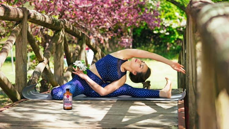 woman doing yoga with kombucha