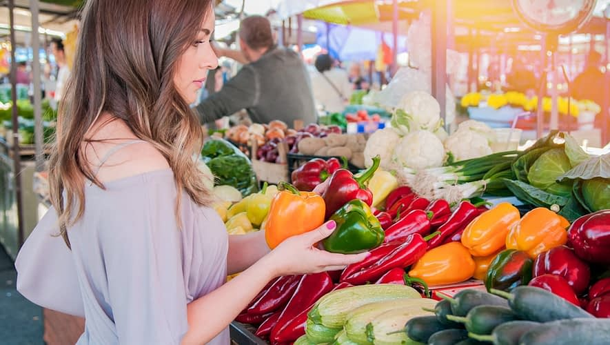 Girl shopping for produce at farmer's market with plant-based diet grocery list