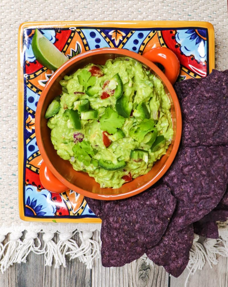 guacamole dip with tomatoes and green peppers