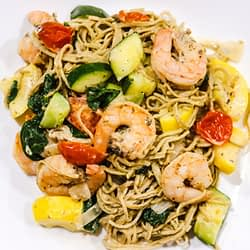 edamame linguins mixed with shrimps, zucchini, and tomatoes, served on a white plate