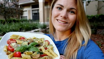 Caitlin Havener holds a Pesto Brown Rice Quinoa Pasta with Italian Chicken Sausage
