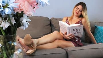 Caitlin reading How Not To Diet by Dr. Greger