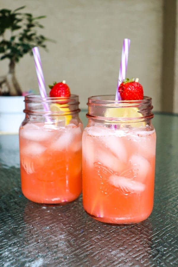 strawberry detox lemonade tall view on patio with bonsai tree in background