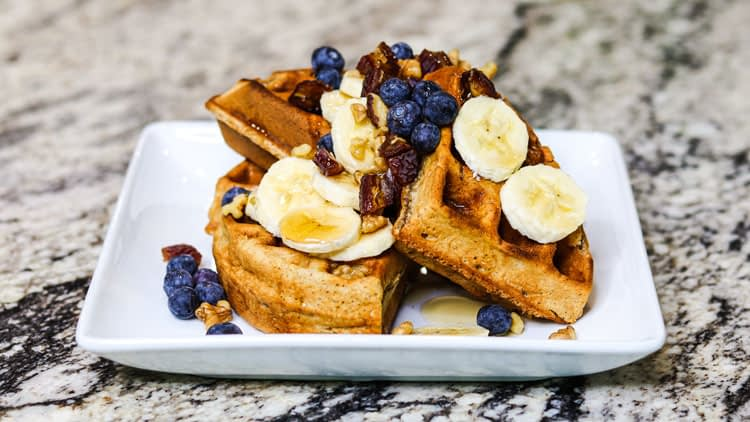 Spelt waffles with maple syrup, banana, blueberry, dates and walnuts