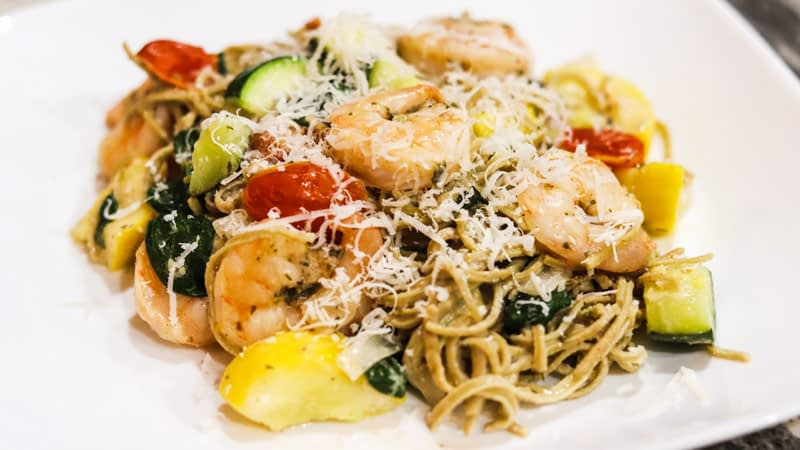 white plate with edamame linguini mixed with shrimps, zucchini, tomatoes, and shredded parmesan on top