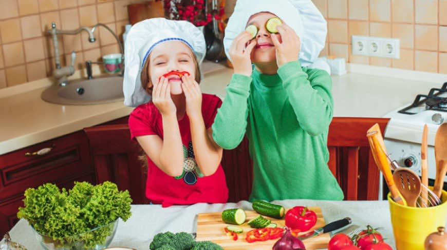 Kids playing with the vegetables in the kitchen